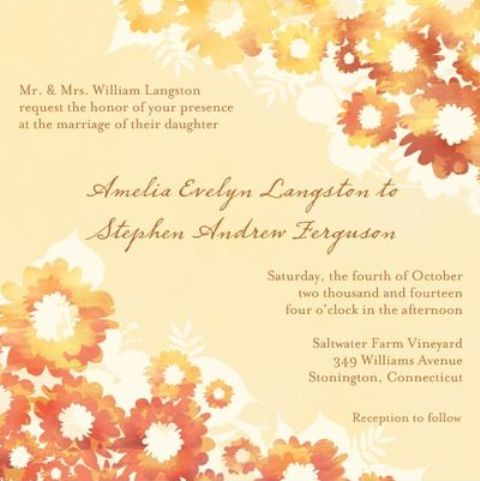 a neutral wedding invitation with bright and bold fall flowers printed on it