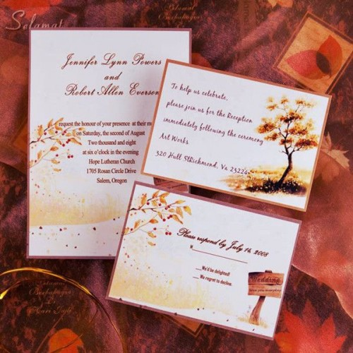 a bright fall wedding invitation suite with fall leaves, branches and trees plus a sign printed on it