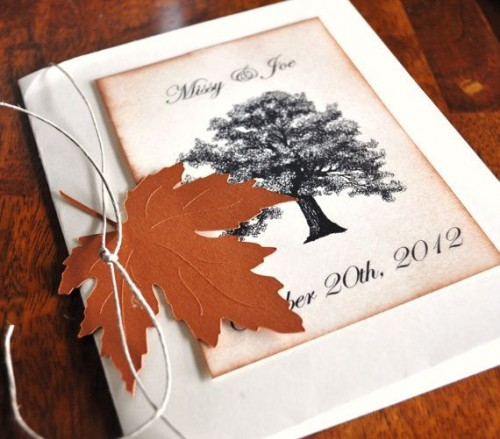 a bold fall wedding invitation suite with a printed tree and a bold fall leaf attached to the suite
