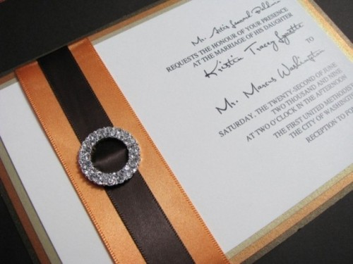 an elegant wedding invitation with orange and brown stripes and an embellished buckle