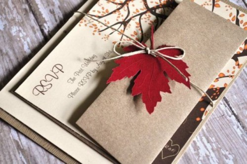 neutral fall wedding invitations with tress and colorful fall leaves attached with twine