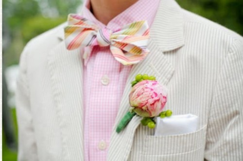 a fresh and bright take on a summer groom's look with an off-white suit, a pink shirt, a colorful bow tie and a floral boutonniere