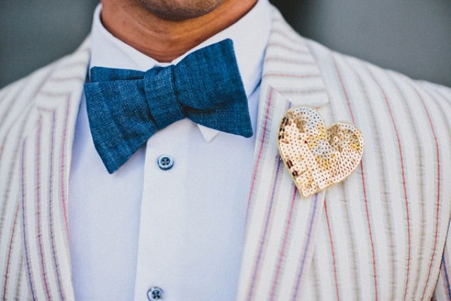 a whimsy groom's look with a striped jacket, a bold blue bow tie and a sequin heart shaped boutonniere