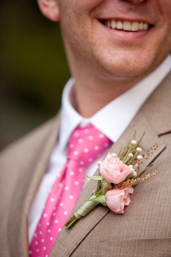 a light brown suit with a pink polka dot tie, a floral boutonniere and a white shirt