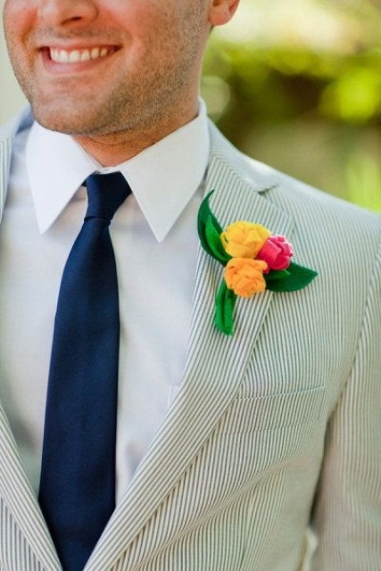 a fresh summer wedding outfit with a grey thin stripe suit, a navy tie and a colorful boutonniere