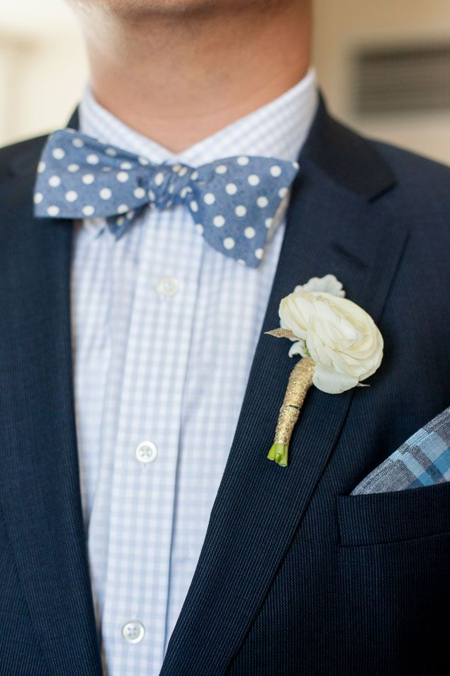 a bold look with a touch of whimsy, a navy suit, a plaid light blue shirt and a blue polka dot bow tie