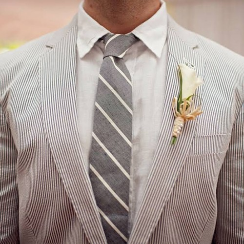 a striped outfit with a thin stripe grey suit, a white shirt and a striped grey tie