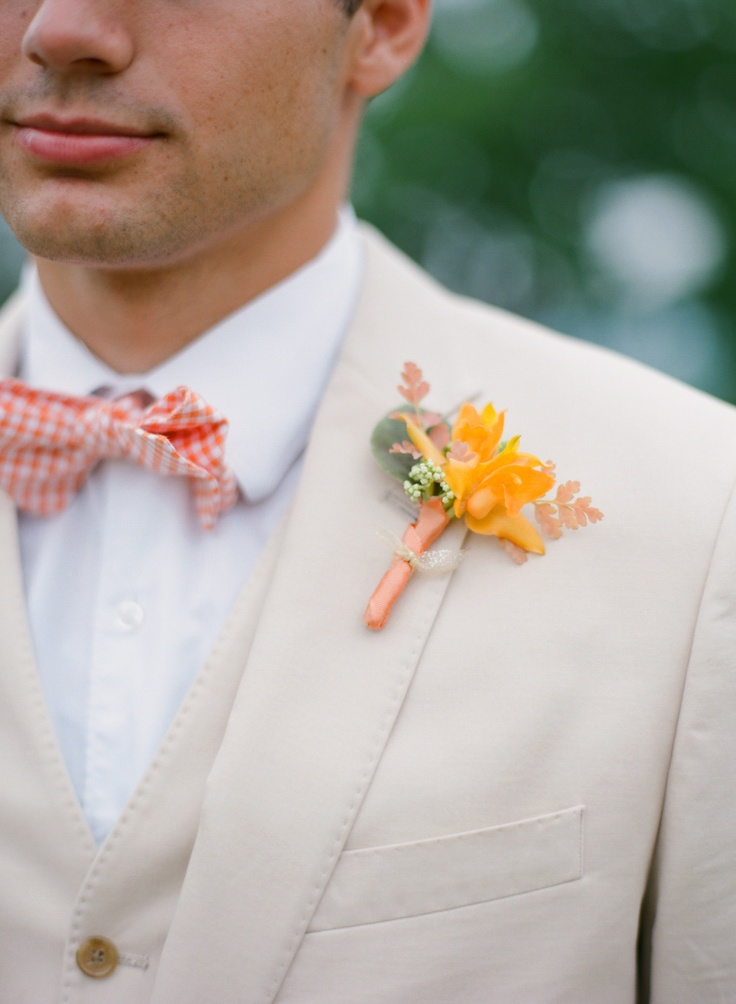 a creamy groom's three piece suit with a white shirt, an orange plaid bow tie and orange boutonniere
