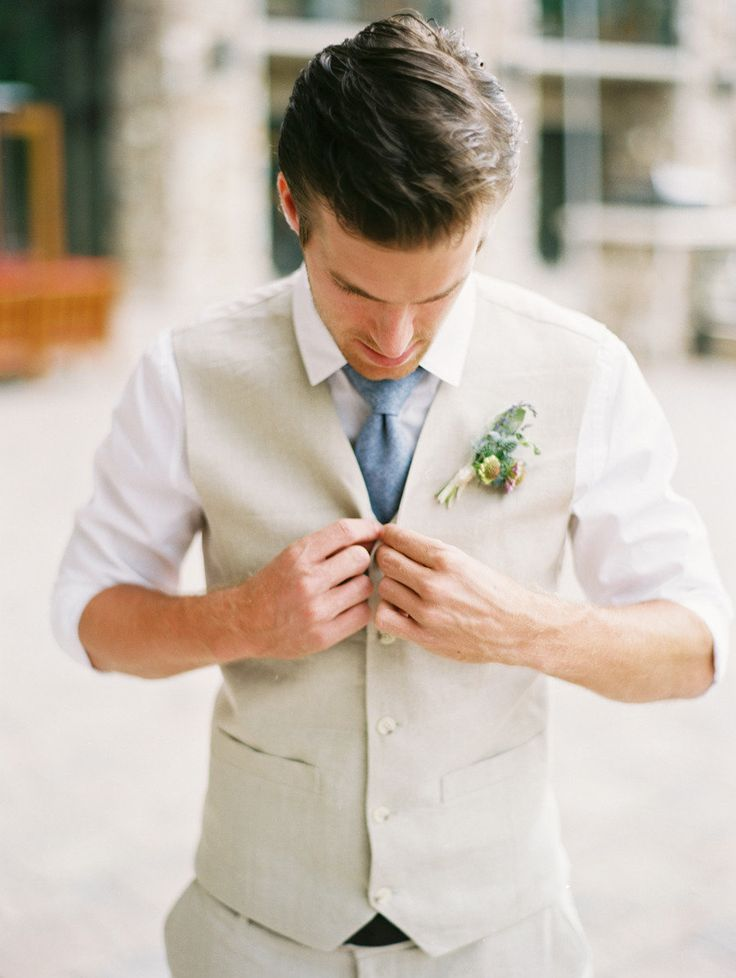 a simple neutral groom's outfit with a tan waistcoat, a blue tie and a white shirt