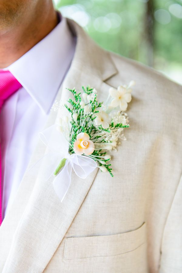 a creamy two piece suit, a bright pink tie, a floral boutonniere for summer