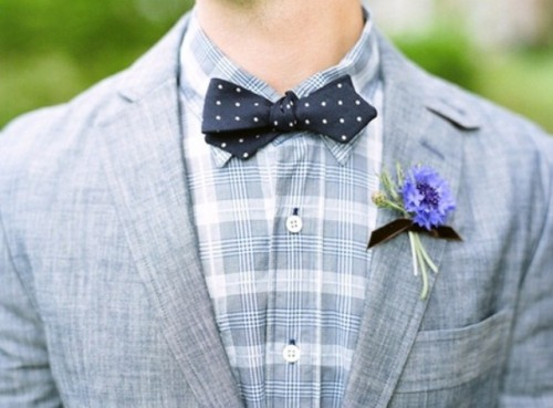 a grey suit, a plaid grey shirt, a navy polka dot bow tie and a bold floral boutonniere