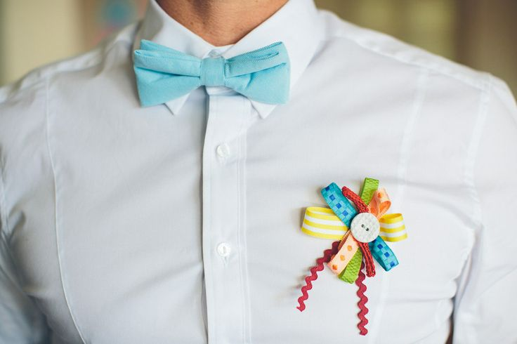 a white shirt, no jacket, a blue bow tie, a colorful boutonniere for a cheerful touch to your summer look