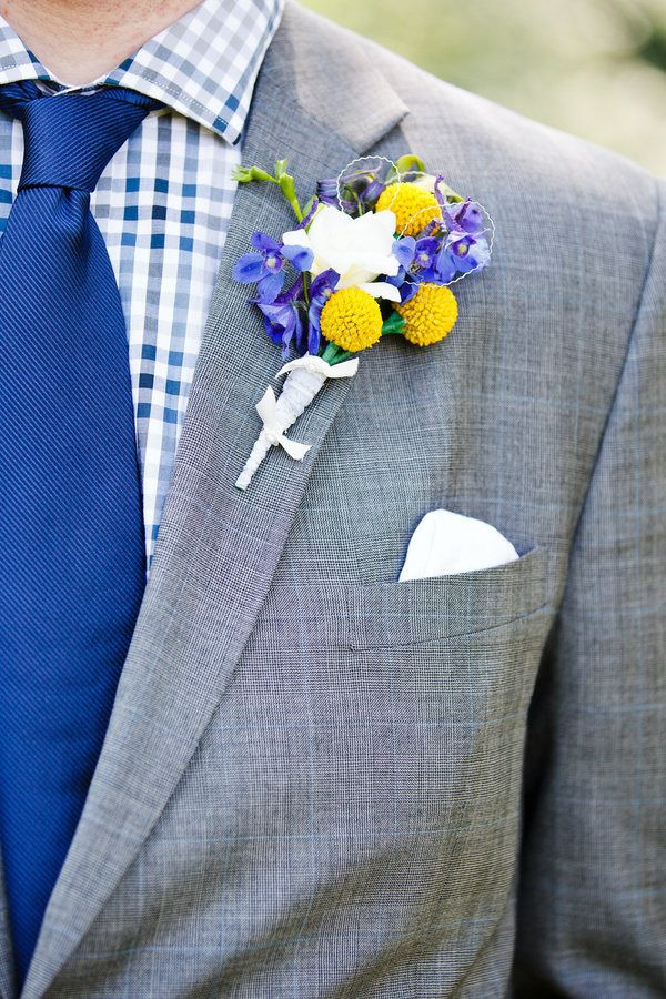 a grey suit, a plaid blue shirt, a bold blue tie and a colorful floral boutonniere for summer