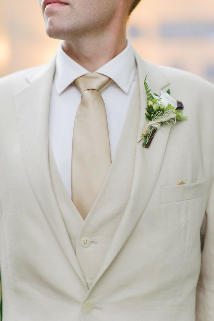 a neutral and formal groom's look with three pieces, a neutral tie and a white shirt for a more formal summer wedding