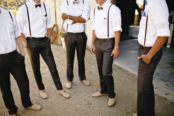 a groom and groomsmen wearing pants, shirts, suspenders and bow ties not to oversweat on a hot day