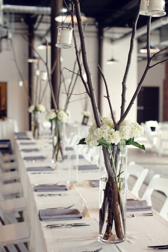 chic minimalist wedding centerpieces of branches and white hydrangeas plus candle lanterns