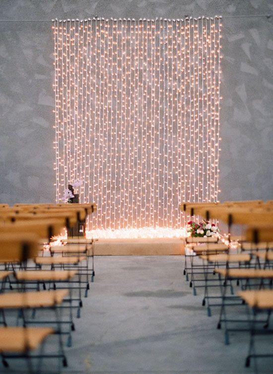 a minimalist wedding backdrop of a wall of lights is a chic idea for a minimalist or modern wedding