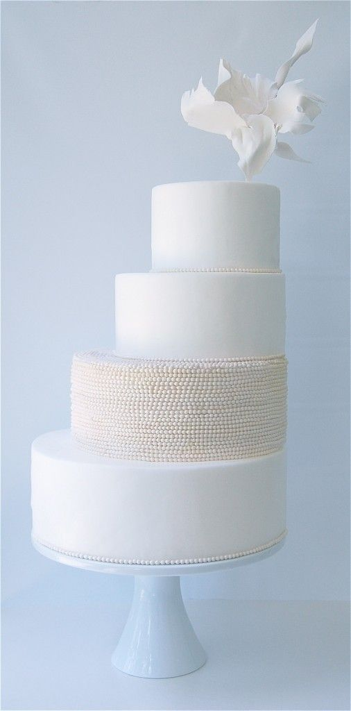 an airy minimalist wedding cake in white and neutrals with a textural tier and a sugar bloom on top