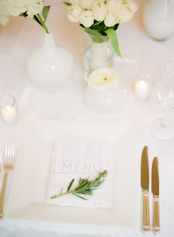 a minimalist wedding tablescape with a greenery twig, white bloom centerpieces and candles