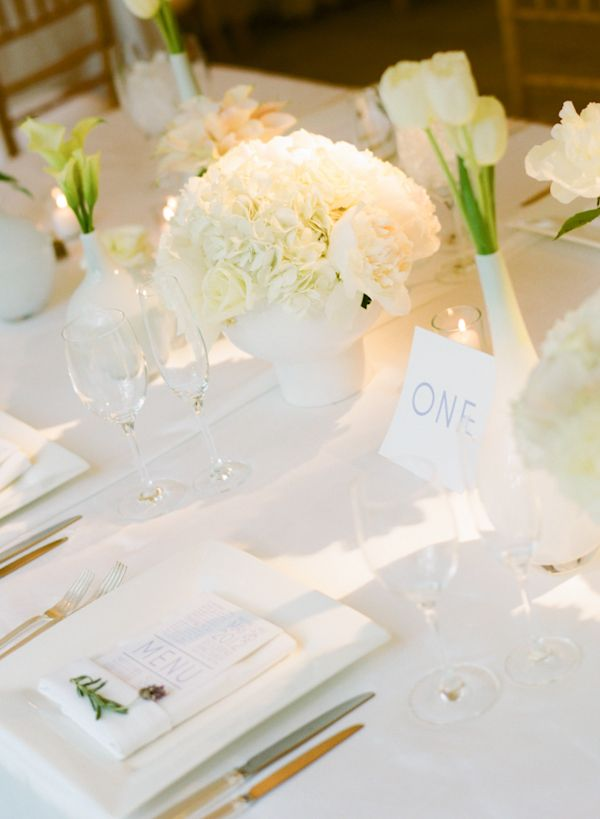 a neutral minimalist wedding tablescape with white bloomsin matte white vases and white candles