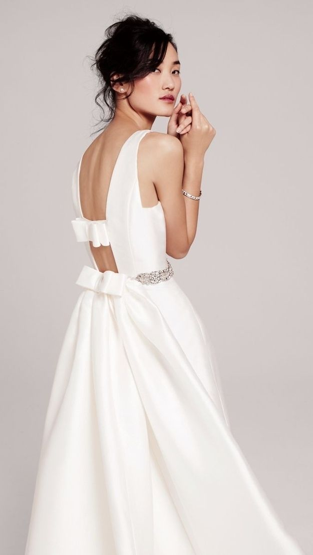 a minimalist white plain wedding dress with an A line silhouette, a cutout back with bows and an embellished sash