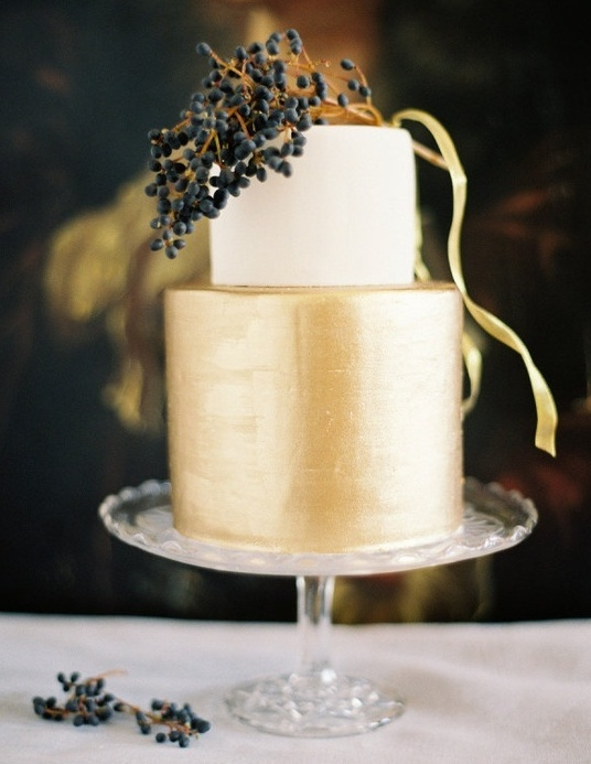 a stylish minimalist wedding cake with a white and gold tier and some berries on top