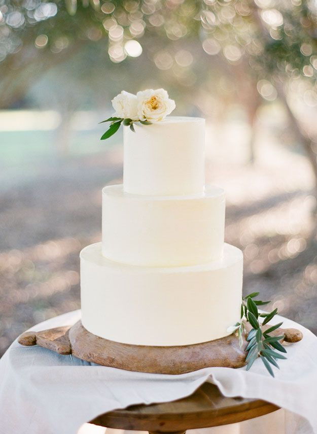 a minimalist white wedding cake topped with neutral blooms and some foliage