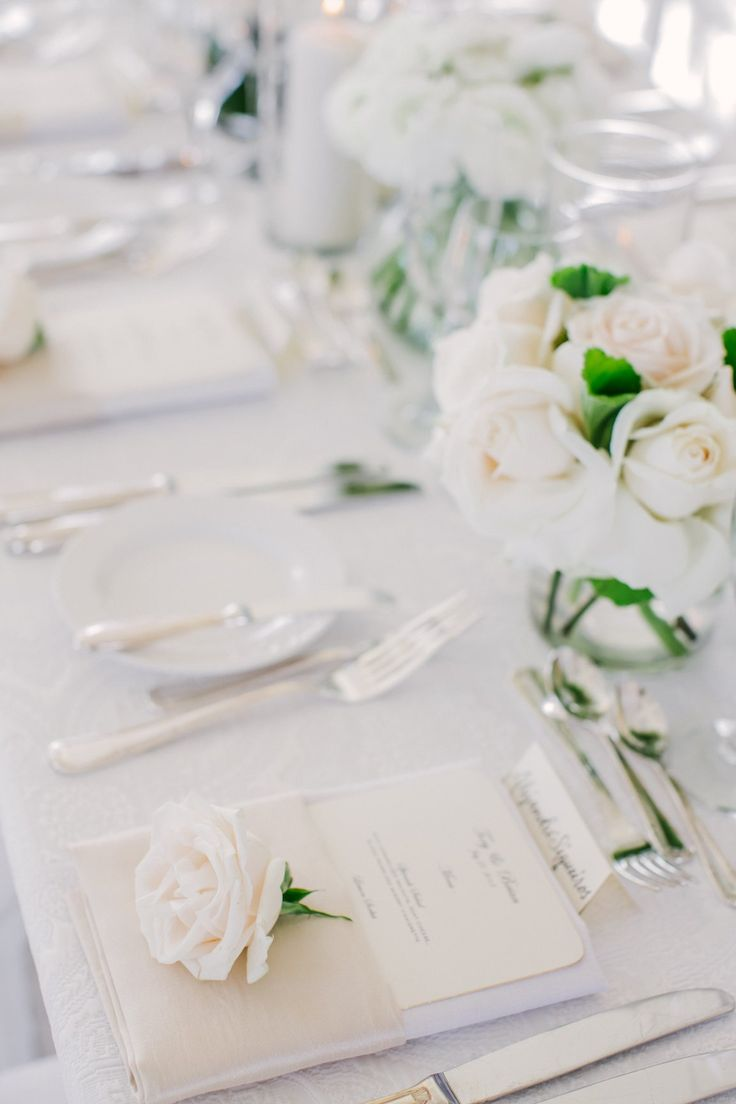 a minimalist neutral tablescape with a neutrla floral centerpiece, menus and white pillar candles