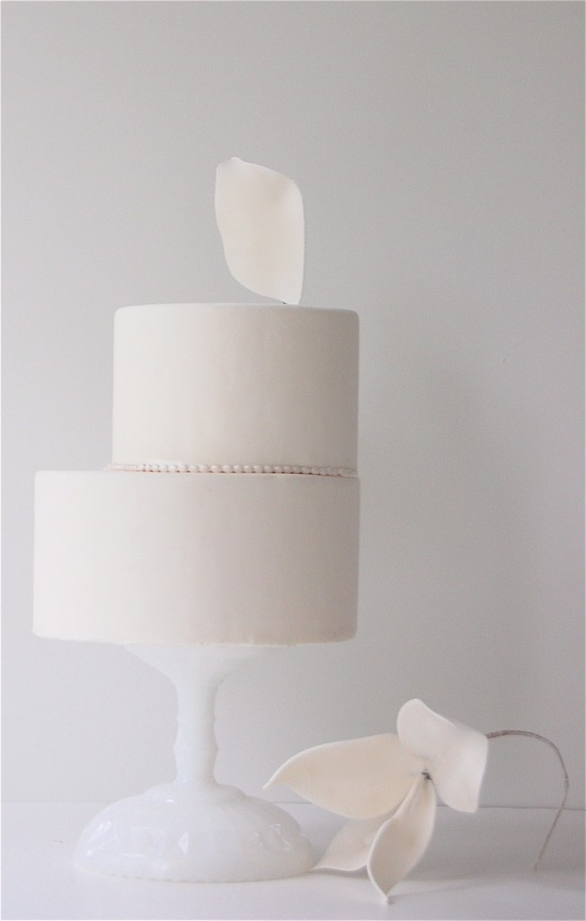 a minimalist white wedding cake with creative asymmetry and a sugar white petal on top for a refined touch