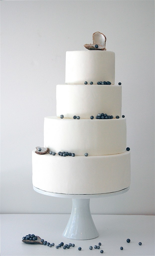 a minimalist coastal wedding cake in white decorated with blue edible pearls and a pearl in a shell on top