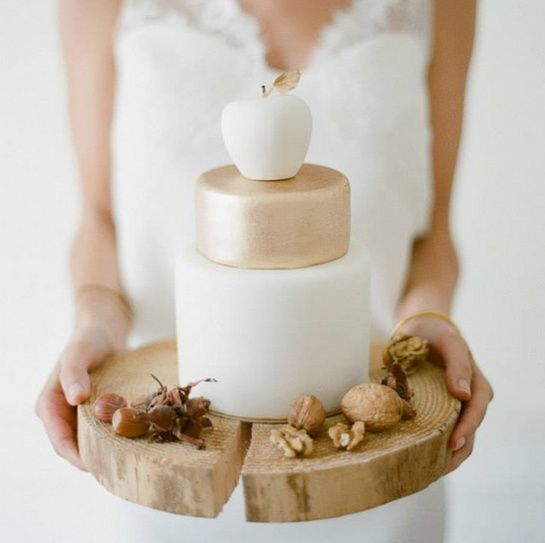 a minimalist fall wedding cake in gold and white and with a sugar white apple on top