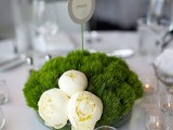 a minimalist wedding centerpiece of moss and white blooms plus candles in bubble candle holders around