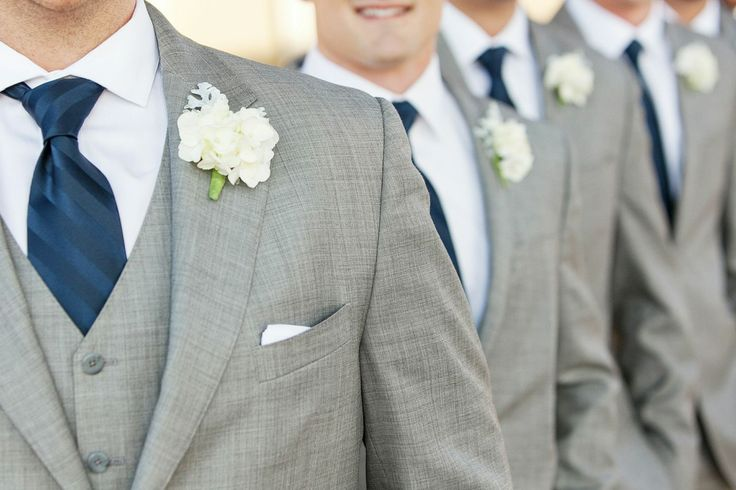 groomsmen wearing three piece grey suits with white shirts and boutonnieres and navy ties