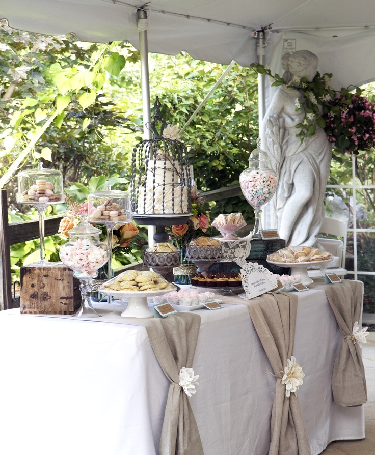 burlap runners, a cake in a cage, sweets in jars and a sculpture with flowers make the dessert table very beautiful