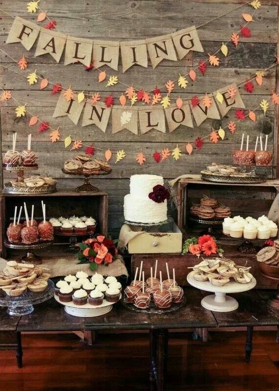 a fall dessert table with burlap garlands, bright leaf garlands, crates and a wooden table for serving food