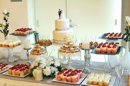 a simple and elegant dessert table styled with a white tablecloth, with glass and silver sweet holders looks chic