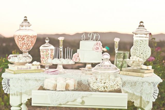 an elegant vintage dessert table with doilies, large jars, vintage stands on a simple table looks chic and elegant