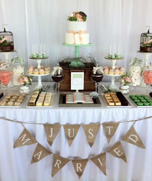 a rustic wedding dessert table with burlap garlands, faux nests, cages and colorful sweets