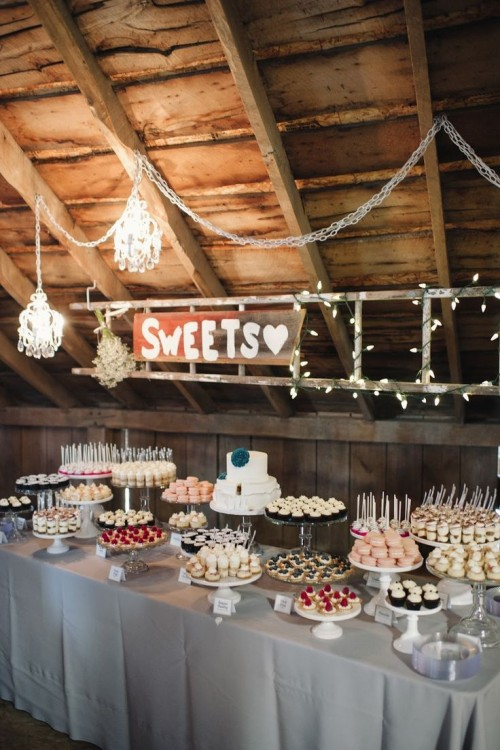 a chic wedding dessert table with lights, elegant chandeliers, a rustic sign and a table with lots of sweets