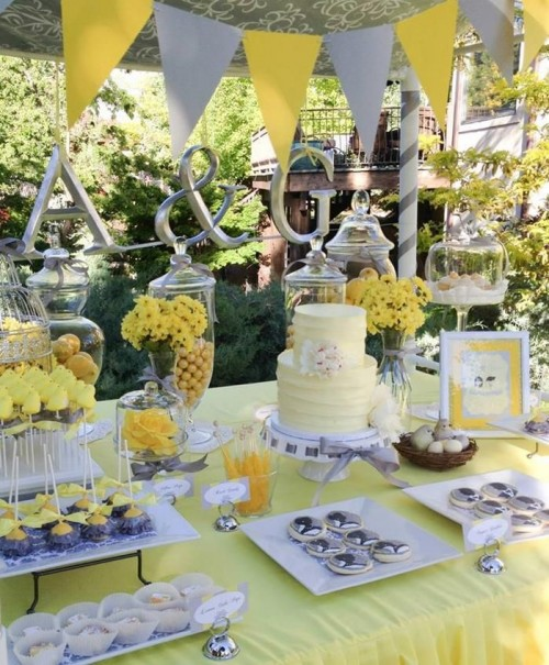 a yellow and grey dessert table with a banner, artworks and yellow flowers, a yellow cake and silver sweets