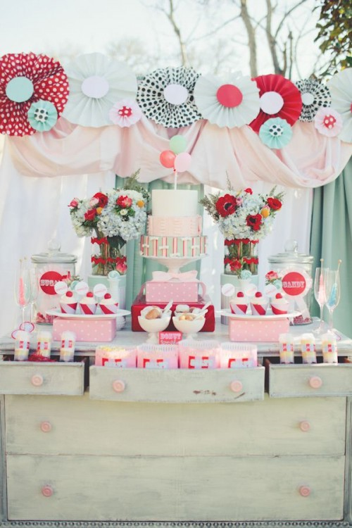 a sweet retro wedding dessert table with red, mint and grey paper fans, bright bloom arrangements, colorful popcorn paper bags
