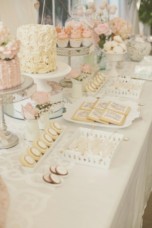 a white and blush wedding dessert table with blush roses and tasty romantic sweets in simple white porcelain