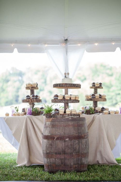 a rustic dessert table with wood slice stands for sweets, a barrel with sweets and some potted greenery