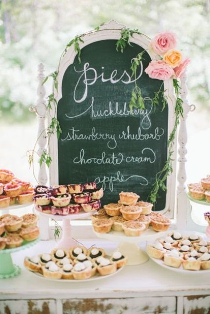 a vintage dessert table with a chalkboard covered with greenery and pink blooms and lots of homey sweets
