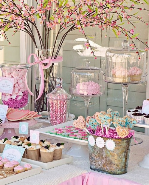 a whimsical dessert table with blooming cherry blossom, lots of pink blooms, pink bows, ribbons and accents