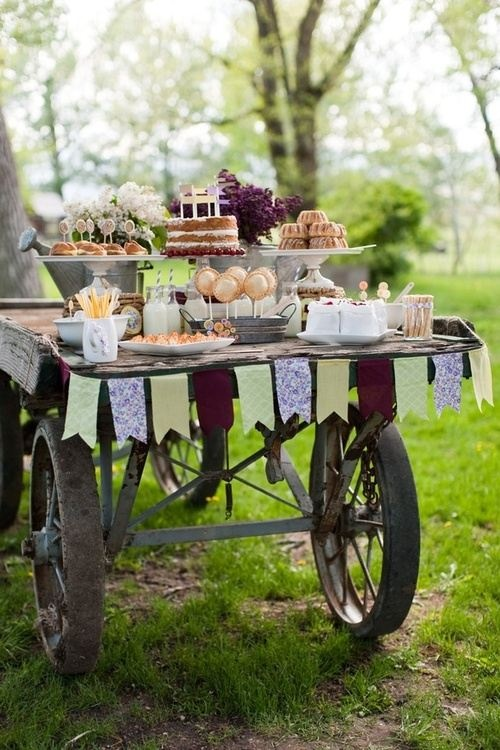 a rustic cart wedding dessert table with a colorful banner, stands with sweets and bright blooms in vases