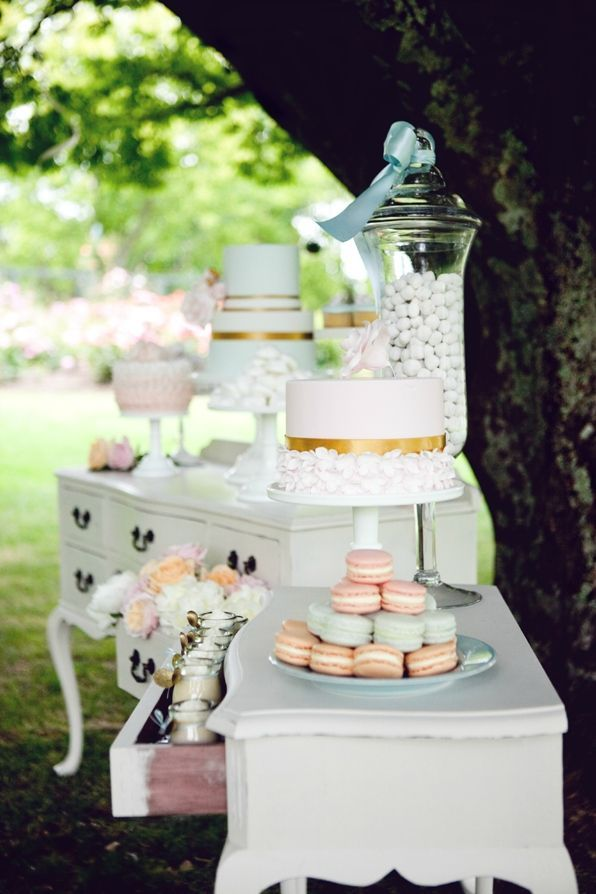 an elegant vintage dessert table composed of two white sideboards and simple white stands for sweets