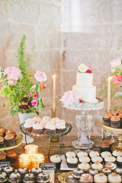 a wedding dessert table with lots of blooms, candles, greenery and simple plates and stands for sweets