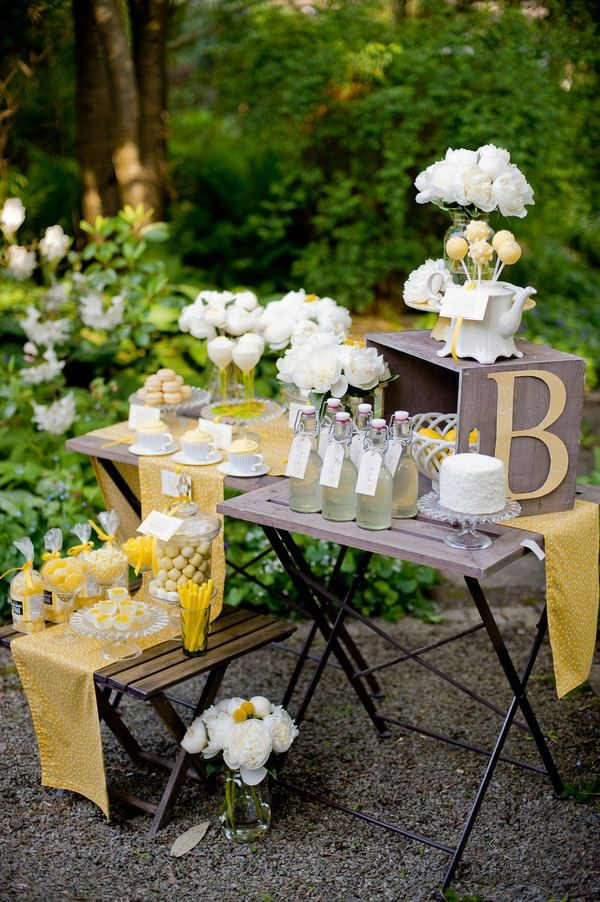 a rustic dessert table of a folding table and stool, yellow linens, a yellow monogram, white and yellow floral arrangements