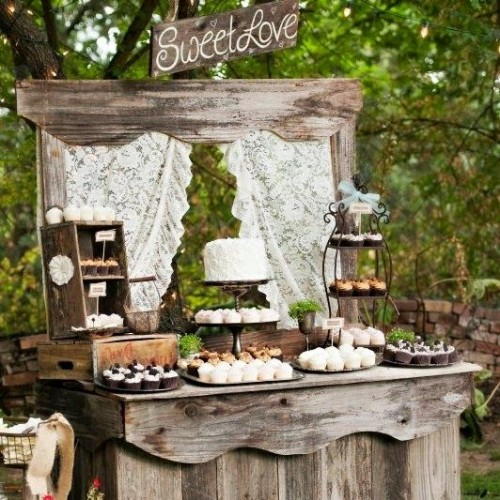 a rustic wedding dessert table of weathered wood, with crates and boxes and lots of sweets